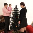 Father, mother and daughter decorating Christmas tree — Stock Video