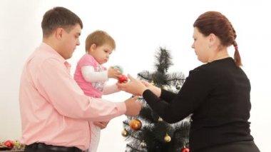 отец, мать и дочь возле елки. — Стоковое видео