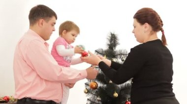 Baba, anne ve kızı yılbaşı ağacı yakınındaki. — Stok video
