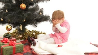 Child waiting for Christmas under a Christmas tree. Waiting for a holiday. — Vídeo de stock