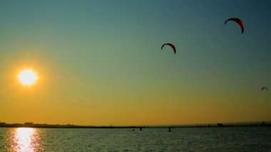 Kitesurfers surfing above the sea at sunset. Kitesurfers at sunset. — 图库视频影像