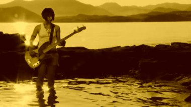 Rock musician playing on the shore. Rock musician. Sepia toned. — Stock Video