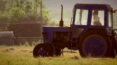 Tractor working in a field on a sunny day. Tractor in a field. — Stok video
