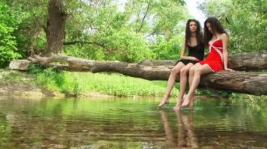 Sisters sitting on a riverside and splashing — Stock Video