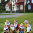 Seven Dwarfs on the lawn on a background house — Stock Photo