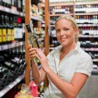 Woman in a supermarket wine shelf — Stock Photo #12582479