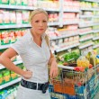 Woman with shopping cart in the supermarket — Stock Photo #12582490