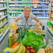 Stock Photo: Woman with shopping cart in the supermarket