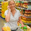 Woman with shopping cart in the supermarket — Stock Photo #12582513