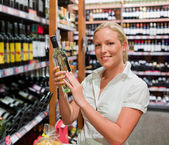 Woman in a supermarket wine shelf — Stock Photo