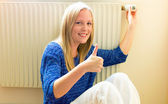Woman sitting in front of a radiator — Stock Photo