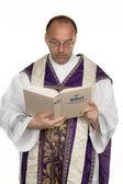 Katolsk präst med bibeln i kyrkan — Stockfoto