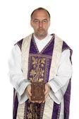 Catholic priest with bible in church — Zdjęcie stockowe