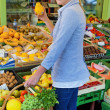 Woman at the fruit market with basket — Stock Photo #13553465