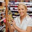 Royalty-Free Stock Photo: Woman in a supermarket wine shelf