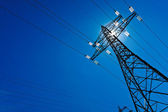 Electricity pylon with sun and sky — Stock Photo