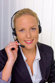 Friendly woman with headset in customer service — Stock Photo