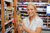 Woman in a supermarket wine shelf — Stock Photo