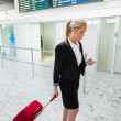 Businesswoman using cell phone at airport — Stock Photo