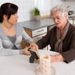 Stock Photo: Woman consoling the widow of death. bereavement support.