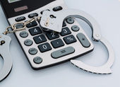 Calculators and handcuffs — Stock Photo