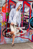 Cool-looking young man in front of graffiti — Stockfoto