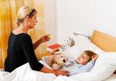 Mor och sjuka barn i sängen. influensa. — Stockfoto