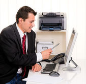 Businessman in office with computer — Stock Photo