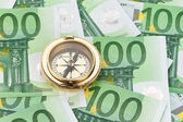 Euro banknotes with a compass — Stock Photo
