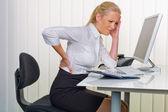 женщины в офисе с болями в спине — Стоковое фото
