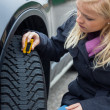 Woman measures tire tread of a car tire — Stockfoto