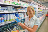 Woman buying milk at the grocery store — Stock Photo
