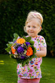 Child with flowers. gift for mothers — Stock Photo