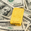 Gold bars on dollar bills - Foto Stock