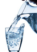 Glass with water and jug — Stock Photo