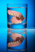 Dentures in a water glass — Stock Photo