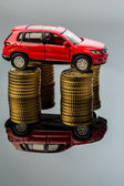 Rising motoring costs. car on coins — Stock Photo