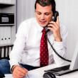 Businessman in office with telephone — Stockfoto