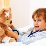 Sick child examined teddy with stethoscope — Stock Photo