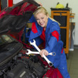 Foto Stock: Woman as a mechanic in auto repair shop