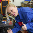 Woman as a mechanic in auto repair shop — Stock Photo #25446085