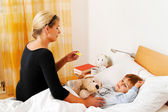 Mother and sick child in bed. flu. — Stock Photo