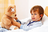 Sick child examined teddy with stethoscope — Stock Photo
