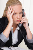 Frustrated woman with phone in office — Stok fotoğraf