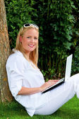 Woman with laptop computer in the garden — Stock Photo