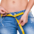 Woman with measuring tape before the next diet - Stock Photo