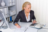 Woman in office with calculator — Stock Photo