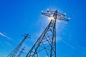 Electricity pylon against blue sky with sun — Stock Photo