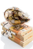 Piggy bank on euro banknotes — Stock Photo