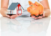 Woman with house and piggy bank — Stock Photo
